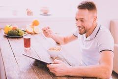 Hübscher netter Mann, der zu Hause frühstückt lizenzfreie stockfotos