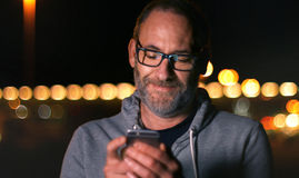 Hübscher reifer Mann, der herein am intelligenten Telefon bei Herbstsonnenuntergang spricht Stockbilder