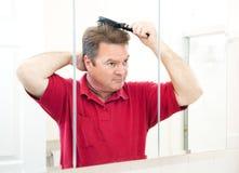 Hübscher reifer Mann, der sein Haar bürstet Lizenzfreie Stockfotos