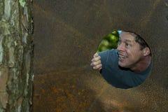 Hübscher reifer Mann im Eisenplattenloch, weg schauend, Grinsen, glücklich, zufrieden gestellt stockfoto
