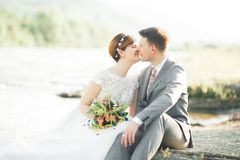 Hübscher romantischer Bräutigam und schöne Braut, die nahe Fluss in den szenischen Bergen aufwirft stockbilder