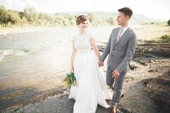 Hübscher romantischer Bräutigam und schöne Braut, die nahe Fluss in den szenischen Bergen aufwirft lizenzfreies stockbild