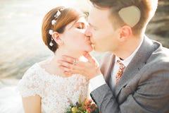 Hübscher romantischer Bräutigam und schöne Braut, die nahe Fluss in den szenischen Bergen aufwirft lizenzfreie stockbilder