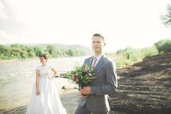 Hübscher romantischer Bräutigam und schöne Braut, die nahe Fluss in den szenischen Bergen aufwirft lizenzfreie stockfotos