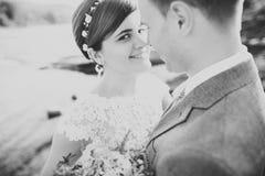 Hübscher romantischer Bräutigam und schöne Braut, die nahe Fluss in den szenischen Bergen aufwirft stockfotos