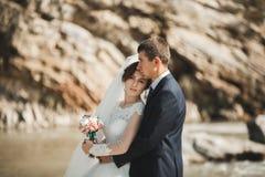 Hübscher romantischer Bräutigam und schöne Braut, die nahe Fluss in den szenischen Bergen aufwirft stockfoto