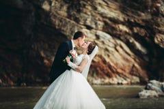 Hübscher romantischer Bräutigam und schöne Braut, die nahe Fluss in den szenischen Bergen aufwirft lizenzfreies stockfoto
