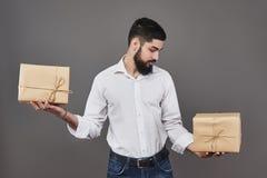 Hübscher romantischer Kerl betrachtet Kasten und trifft eine Wahl Eine große Geschenkbox zwei für seine Paare, auf Grau halten lizenzfreie stockfotografie