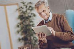 Hübscher Ruhestand unter Verwendung seiner Tablette lizenzfreie stockbilder