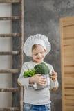 Hübscher schöner Junge, der einen Topf voll vom Gemüse hält Gesunde Nahrung Kleiner Chef der Ernte stockfoto