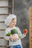 Hübscher schöner Junge, der einen Topf voll vom Gemüse hält Gesunde Nahrung Kleiner Chef der Ernte stockbild