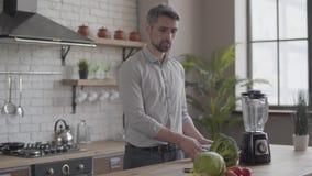 Hübscher schöner Mann im Hemd Abendessen kochend Rezept auf der Tablette in der Küche zu Hause überprüfend Konzept von stock footage