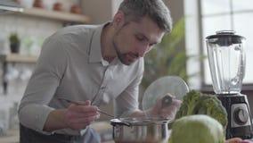Hübscher schöner Mann im Hemd Suppe in der Küche kochend Konzept der gesunden Nahrung, Hausmannskost Der Kerl stock video footage