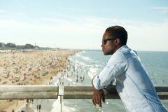 Hübscher schwarzer Mann mit der Sonnenbrille, die am Strand sich entspannt Lizenzfreies Stockfoto