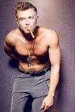 Hübscher sexy junger Mann mit dem nackten Torso, der eine Zigarre raucht Stockfotografie
