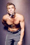 Hübscher sexy junger Mann mit dem nackten Torso, der eine Zigarre raucht Stockfotos
