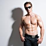 Hübscher sexy Mann in den Gläsern, die am Studio aufwerfen Lizenzfreie Stockfotografie