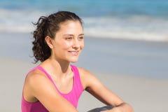 Hübscher Sitz Brunette, der neben dem Meer sitzt Lizenzfreie Stockfotos