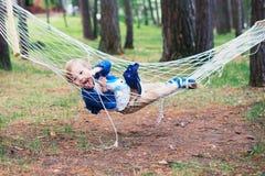 Hübscher smilling Junge, der auf hammok im Wald stillsteht Lizenzfreies Stockbild