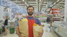Hübscher Speicherangestellter im roten aport mit den Lebensmittelgeschäftpapiertüten, die im Supermarkt stehen, lächelt er an der stock video