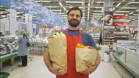 Hübscher Speicherangestellter mit den Lebensmittelgeschäftpapiertüten, die im Supermarkt stehen, lächelt er an der Kamera stock footage