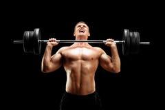 Hübscher Sportler, der ein Schwergewicht anhebt Stockbilder