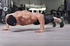 Hübscher starker athletischer Mann, den die Ausführung drücken, ups an der Turnhalle lizenzfreie stockfotos