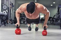 Hübscher starker athletischer Mann, den die Ausführung drücken, ups mit Kesselglocke lizenzfreies stockfoto