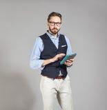 Hübscher stilvoller bärtiger Mann in der klassischen Weste, die Tablette hält Lizenzfreie Stockbilder