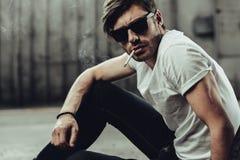Hübscher stilvoller junger Mann in der Sonnenbrille, die am Betrachten der Kamera raucht Lizenzfreie Stockfotografie
