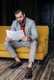 hübscher stilvoller Mann in der modischen dem Klagenlesezeitung und -sitzen Lizenzfreies Stockbild
