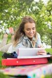 Hübscher Student, der auf dem Gras studiert mit ihrem Tabletten-PC liegt Stockfotos
