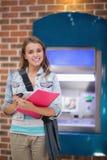 Hübscher Student, der an der Kamera am ATM lächelnd steht Stockfotos