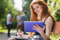 Hübscher Student, der draußen auf dem Campus studiert Lizenzfreie Stockfotos