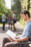 Hübscher Student, der draußen auf dem Campus studiert Stockfoto