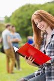 Hübscher Student, der draußen auf dem Campus studiert Lizenzfreies Stockfoto