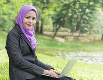 Hübscher Student, der an ihrem Laptop beim Stillstehen im Park arbeitet Stockbild