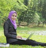 Hübscher Student, der an ihrem Laptop beim Stillstehen im Park arbeitet Stockfoto