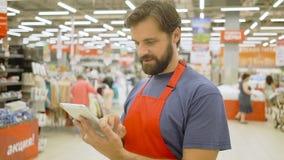 Hübscher Supermarktsekretär unter Verwendung einer Touch Screen Tablette im Supermarkt, lächelt er an der Kamera stock footage