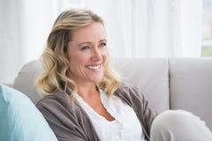 Hübscher Tag blondes Sitzen auf der Couch träumend Stockfoto