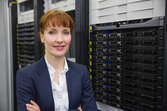 Hübscher Techniker, der an der Kamera neben Serverturm lächelt Lizenzfreie Stockfotografie