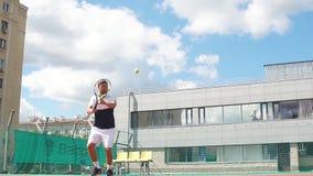 Hübscher Tennisspieler mit Schläger und Ball auf öffentlicher Sitzung bringt den Aufschlag zurück stock footage