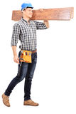 Hübscher Tischler, der ein paar Planken trägt Lizenzfreie Stockfotografie