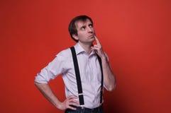 Hübscher träumerischer Mann im Hemd und im schwarzen Hosenträger stockfotografie