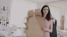 H?bscher und gl?cklicher brunette Modedesigner, der mit Mustern oder Modellen in eigener n?hender Werkstatt des Tageslichts arbei stock video