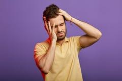 Hübscher unglücklicher Mann, der die starken Schmerz hat und Kopf hält stockbild