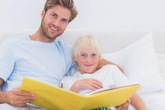 Hübscher Vater, der eine Geschichte zu seinem Sohn liest Stockbilder