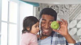Hübscher Vater des Afro, der seinem kleinen Mädchen grünen Apfel gibt stock video footage