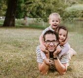 Hübscher Vater mit seinen geliebten Kindern, die im Park stillstehen stockfoto