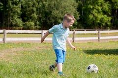 Hübscher Vati mit seiner kleinen netten Sonne haben Spaß und spielen amerikanischen Fußball auf grünem grasartigem Rasen stockfoto